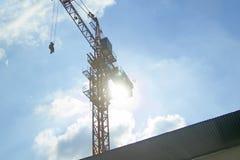 Lyftande kran av omvänt sol- med blå himmel Arkivfoto