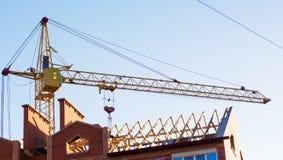 Lyftande kran på bakgrund av byggnad under konstruktion Ne Royaltyfri Bild