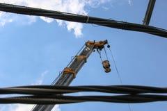 Lyftande kran på blå himmel med förgrund för elektrisk kabel Fotografering för Bildbyråer