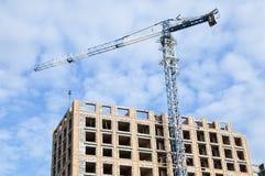 Lyftande kran på konstruktionen av ett höghus arkivfoton