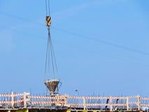 Lyftande kranen levererar den konkreta hinken till konstruktionsplatsen till p Arkivfoto