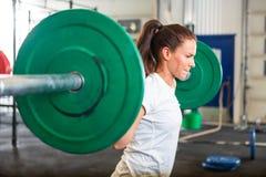 Lyftande skivstång för färdig kvinna i idrottshall Royaltyfri Foto