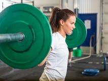 Lyftande skivstång för färdig kvinna i idrottshall Fotografering för Bildbyråer