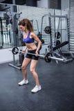 Lyftande skivstång för muskulös kvinna arkivfoto