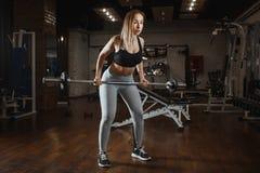 Lyftande skivstång för ung kvinna med ljusa vikter på idrottshallen Kvinnlig görande crossfitgenomkörare för kondition royaltyfria foton