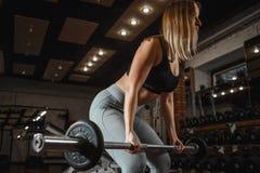 Lyftande skivstång för ung kvinna med ljusa vikter på idrottshallen Kvinnlig görande crossfitgenomkörare för kondition fotografering för bildbyråer