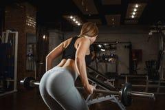 Lyftande skivstång för ung kvinna med ljusa vikter på idrottshallen Kvinnlig görande crossfitgenomkörare för kondition royaltyfri bild