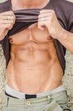Lyftande skjorta för sexig ung muskulös man som visar abs Arkivfoto