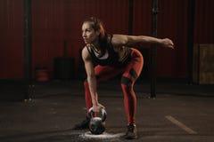 Lyftande skurkrollvikter f?r kvinnlig idrottsman nen Sportkvinna som rymmer kettlebell medan crossfitutbildning arkivbilder
