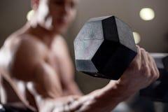 Lyftande vikt för ung vuxen kroppsbyggare i idrottshall Arkivfoton