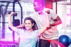 Lyftande vikter för idrotts- kvinna som hjälps av instruktören Arkivfoton