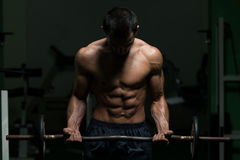 Lyftande vikter för macho man med skivstången Arkivfoton