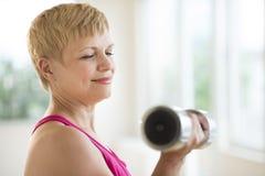 Lyftande vikter för mogen kvinna Fotografering för Bildbyråer