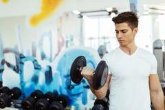 Lyftande vikter för stilig man i idrottshall Arkivbilder