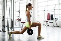 Lyftande vikter för ung härlig kvinna i en idrottshall Royaltyfria Foton