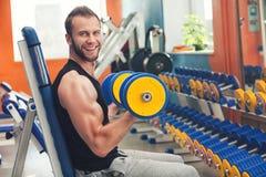 Lyftande vikter för ung idrottsman nen i idrottshallen royaltyfri bild