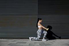 Lyftande vikter för idrotts- kvinnlig, medan utarbeta mot väggen med kopieringsutrymme för ditt textmeddelande Arkivbild