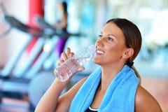 lyftande weights le för attraktiv kameracloseupkondition kvinnan Härlig ung flicka i idrottshalldricksvattnet, med den blåa handd Arkivbild