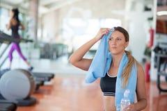 lyftande weights le för attraktiv kameracloseupkondition kvinnan Härlig ung flicka i idrottshalldricksvattnet, med den blåa handd Arkivfoto