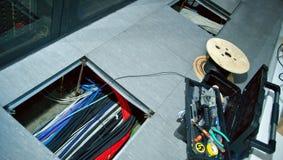 Lyftt golv & x28; löstagbar floor& x29; i serverrummet med en öppen lucka på till luckan är nätverkskablar arkivfoto