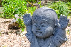 Lyftt rörelse för händer upp av Jizo den lilla stenbuddha statyn royaltyfri fotografi