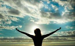 Lyftta armar under solnedgång Royaltyfria Bilder