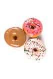 Lyftta frostade donuts Fotografering för Bildbyråer