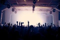Lyftta händer på konserten i en gammal mötesplats Royaltyfri Bild