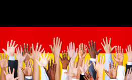 Lyftta multietniska händer och tysk flagga Arkivbild