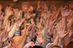 Lyftta upp händer för en människa på händelsen Royaltyfri Bild