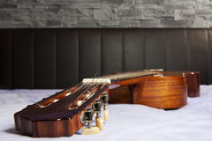 Lying acoustic guitar on bed Stock Photography