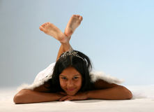 Lying angel. Cute teenage girl dress like an angel lying on the ground againstlight blue background stock image
