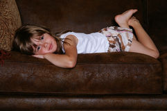 Lying around. A cute young girl lying on a sofa getting ready for a nap stock photo