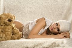 Lying attractive young girl. Attractive young girl is lying on the white counterpane Royalty Free Stock Image