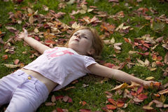 Lying in the Autumn Leaves. A young girl, looking quite fed up, is lying on some autumn leaves Royalty Free Stock Photos