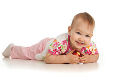 Lying baby girl with red apple. Baby girl with red apple is lying on the floor Royalty Free Stock Image