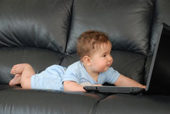 Lying baby with laptop Royalty Free Stock Photos