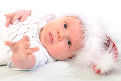 Lying baby in red Christmas hat Stock Images