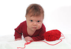 Lying baby with red clew of wool Stock Photos