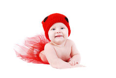 Lying baby in red hat Royalty Free Stock Image