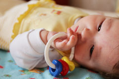 Lying a baby with a toy in his hand Royalty Free Stock Photography