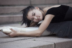 Lying ballerina. The Ballet dancer lying down and stretches on the stairs Royalty Free Stock Photos