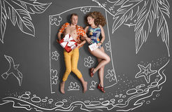 Lying on the beach. Love story concept of a romantic couple against chalk drawings background. Young couple on vacation, lying on the beach and sharing gifts Stock Photography