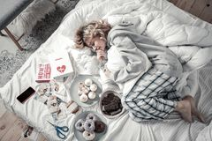 Woman lying in bed near books and food after breakup. Lying in bed. Emotional women wearing pajamas lying in bed near books and food after breakup royalty free stock image