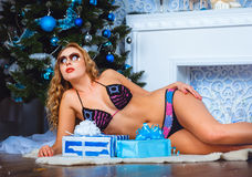 Lying bikini girl with blue and white boxes of gifts Royalty Free Stock Images