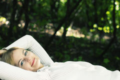 Lying blue-eyed young woman in the forest Royalty Free Stock Photo