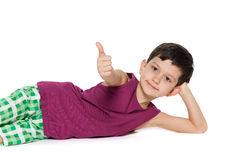 Lying boy holds his thumb up Royalty Free Stock Image