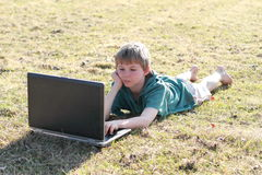 Lying boy interested in a computer Royalty Free Stock Image