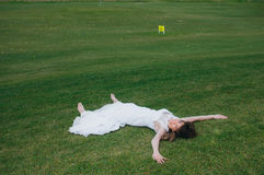 Lying bride in wedding dress on the green field of the golf club. Smiling beautiful bride in wedding dress on the green field of the golf club stock image