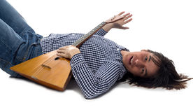 Lying brunette man with balalaika Stock Photography